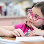 Girl wearing glasses looks off to the side, in a thinking pose, holding a pencil to a paper on a desk