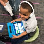 Photo of student seated and working on tablet with headphones