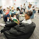 Photo of classroom with students reading on beanbags and working on devices at desks