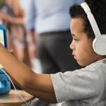 Elementary student sits at desk with headphones on while holding tablet in front of him