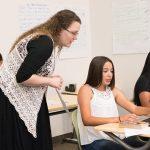 Teacher stands behind student on laptop at desk, looking over student's shoulder as she speaks