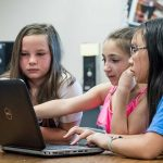 Three female students sit together in front of laptop