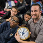 Three students and a teacher smile for the camera, holding school symbol