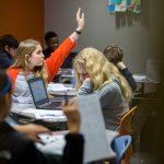 Student raises her hand, sitting among classmates