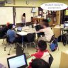 Photo of classroom with indication showing student is signing up for assessment on the whiteboard at front of class